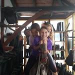 Mehrere Mädchen sitzen auf einem Übungspferd aus Holz und lachen in die Kamera.