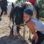 Ein Mädchen lehnt ihren Kopf an den Kopf eines braun-weißen Pferdes und lächelt in die Kamera.