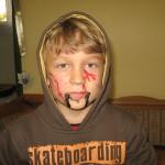Ein Junge ist mit roter unter schwarzer Schminke geschminkt und blinkt streng in die Kamera.