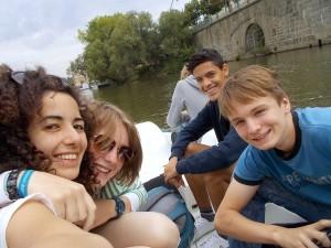 Eine Gruppe Jugendlicher fährt auf einem Boot auf einem Fluß oder See und lacht glücklich gemeinsam in die Kamera