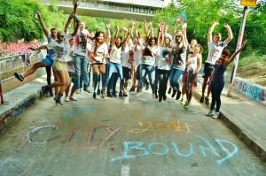 Eine Gruppe Jugendlicher hüpft im Freien in die Höhe in dem Moment als das Foto geschossen wird. Vor Ihnen ist der Schriftzug City Bound 2014 auf der Straße zu lesen.