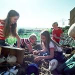 Mehrere Kinder sitzen im Freien auf decken. Um sie herum sind mehrere Kaninchen, um die sich sich liebevoll kümmern und die sie streicheln.