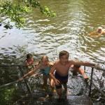 Ein Mädchen und ein Junge steigen an einer Treppe aus einem Naturbadesee. Im Hintergrund sieht man andere Personen schwimmen.