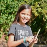 Ein Mädchen hält einen Stock und ein Schnitzmesser in der Hand. Sie lächelt glücklich in die Kamera.