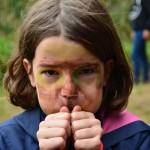Ein Mädchen mit dunkelbraunen schulterlangen Haaren steht in der Natur und hat die Hände so vor den Mund gelegt, dass sie damit pfeifen kann. Es ist nur der Kopf des Mädchens zu sehen, welches mit grüner und brauner Tarnfarbe bemalt ist.