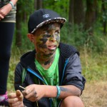 Ein Junge mit dunkler Schildmütze kniet in der Natur und schaut in die Ferne. Sein Gesicht ist mit grüner Tarnfarbe bemalt.
