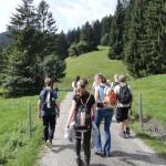 Mehrere Jugendliche beim Wandern in der Natur. Sie sind umgeben von Wiesen und einigen Bäumen.