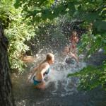 Mehrere Kinder und Jugendliche sind in einem Naturbadesee oder Fluß umgeben von Bäumen. Sie liefern sich gerade eine Wasserschlacht und spritzen sich gerade voll.
