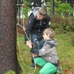 Zwei Jungen arbeiten an einer selbstgebauten Strickleiter, die an einem Baum befestigt ist.