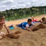Drei Jungen liegen am Sandstrand und buddeln Löcher in den Sand. Im Hintergrund ist ein Badesee zu sehen.