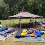 Eine Wiese mit einer offenen Jurte mit einer Lagerfeuerstelle. Um die Jurte herum sind Schlafsäcke verteilt und einige Jugendliche schlafen noch darin. Es ist Morgen und das Lagerfeuer ist bereits ausgegangen.