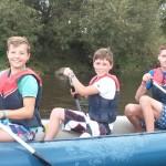 Nahaufnahme von drei Jungen im Tween-Alter in einem Kanu, wie sie gerade auf einem Fluss paddeln und dabei lachen. Im Hintergrund ist ein weiteres Kanu mit mehreren Mädchen an Bord.
