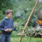 Junge mit kurzen braunen Haaren steht vor einer Kochstelle mit kleinem Feuer und darüberhängendem Kochtopf und beobachtet das Feuer.