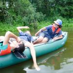 Drei Jugendliche sind auf einem Schlaukanu auf einem See oder Fluss. Sie machen gerade eine Pause und lehnen sich entspannt im Kanu zurück.
