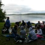Eine Gruppe Jugendlicher sitzt auf einer Wiese. Im Hintergrund ist ein See oder Fluss zu sehen, an dessen Ufer einige Kanus liegen. Die Jugendlichen sitzen im Kreis und essen gemeinsam.