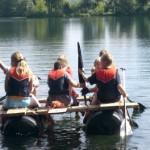 Mehrere Kinder mit Schwimmweste paddeln auf einem See mit einem selbstgebauten Floß