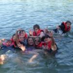 Eine Gruppe Kinder planschen im Wasser und lachen dabei in die Kamera
