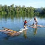 Es sind zwei Kinder mit etwas Abstand auf einem See umgeben von ein paar Holzplanken. Eines steht auf Holzplanken, das andere versucht auf den Holzplanken zu laufen. Es schaut aus, als ob ein selbstgebasteltes Floß auseinander gefallen ist und die beiden Kinder nun mit den Resten des Floßes spielen.