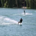 Ein Jugendlicher auf einem See, wie er gerade Wakeboard fährt. Er lehnt sich stark zurück und das Wasser hinter ihm spritzt in die Höhe. Er scheint zu wissen was er tut und scheint nicht das erste Mal auf dem Brett zu stehen.