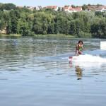 Ein Junge fährt auf einem See Wakeboard. Er wirkt sehr konzentriert und scheint noch nicht lange Wakeboard fahren zu können.