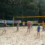 Eine Gruppe Jugendlicher auf einem Beachvolleyballfeld wie sie gerade gegeneinander spielen.