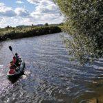 Ein einzelnes Kanu auf einem Fluß mit mehreren Personen an Bord.