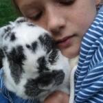 Nahaufnahme eines Mädchens, das ein Kaninchen umarmt. Die Augen des Mädchens sind geschlossen und sie scheint den Moment zu genießen.