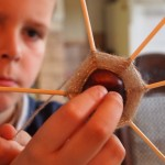 In eine Kastanien wurden mehrere Schaschlikspieße in gleichmäßigen Abständen gesteckt. Ein Junge hält das Konstrukt in die Höhe und wickelt Faden um die Spieße, sodass das Gebilde langsam wie ein Spinnennetz aussieht.