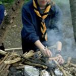 Eine jugendliche Pfadfinderin kümmert sich um das Feuer einer Kochstelle, damit es nicht ausgeht.