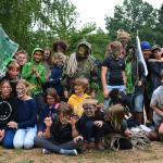 Eine Gruppe Kinder posiert auf einer Wiese vor Bäumen für ein Gruppenfoto. Sie sind in Tarnfarben gekleidet und/oder bemalt. Manche der Kinder ahmen mit Armbewegungen wilde Tier nach.