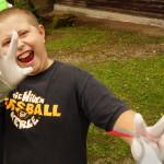 Ein Junge trägt weiße Plastikhandschuhe. In der einen Hand hält er eine Plastiktüte zur Beweissicherung. Mit der anderen Hand zeigt er die Zahl drei an. Er lacht fröhlich.