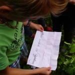 Ein Junge wird von schräg oben gezeigt, wie er einen Zettel mit einem Rätsel in der Hand hält und das Rätsel liest.