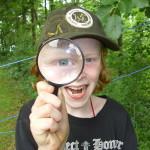 Ein lachender Junge mit Schildmütze hält ein Vergrößerungsglas vor sein Gesicht und schaut hindurch. Durch das Vergrößerungsglas ist sein eines Auge stark vergrößert.