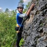 Ein Junge klettert an einem Fels in der Natur. Er schaut froh in die Kamera.