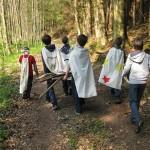 Eine Gruppe läuft mit Umhängen im Wald. Die Kinder sind nur von hinten zu sehen.