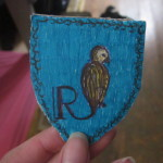 Ein selbstgebasteltes Wappen der Ravenclaws. Ein sitzender Vogel auf blauem Hintergrund mit dem