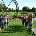 Zwei Kindergruppen stehen sich auf einer Wiese gegenüber und zeigen mit Zauberstäben aufeinander.