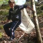 Ein Junge mit weißem Umhang geht einen steilen Abhang im Wald hinunter und hält sich zur Stabilisation an einem Baum fest.