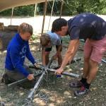 Zwei Teamer und ein Junge beugen sich über Zeltmaterial. Sie binden gerade die Stangen für das Zelt zusammen.