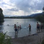 Eine Gruppe Kinder und Jugendlicher am Rand eines Sees. Einige schwimmen bereits, andere laufen gerade ins Wasser.