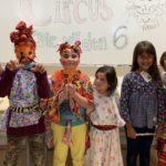 Mehrere Kinder stehen in bunter Verkleidung und mit selbstgebastelten Tiermasken oder bemaltem Gesicht vor einem Whiteboard. Auf dem Whiteboard steht: