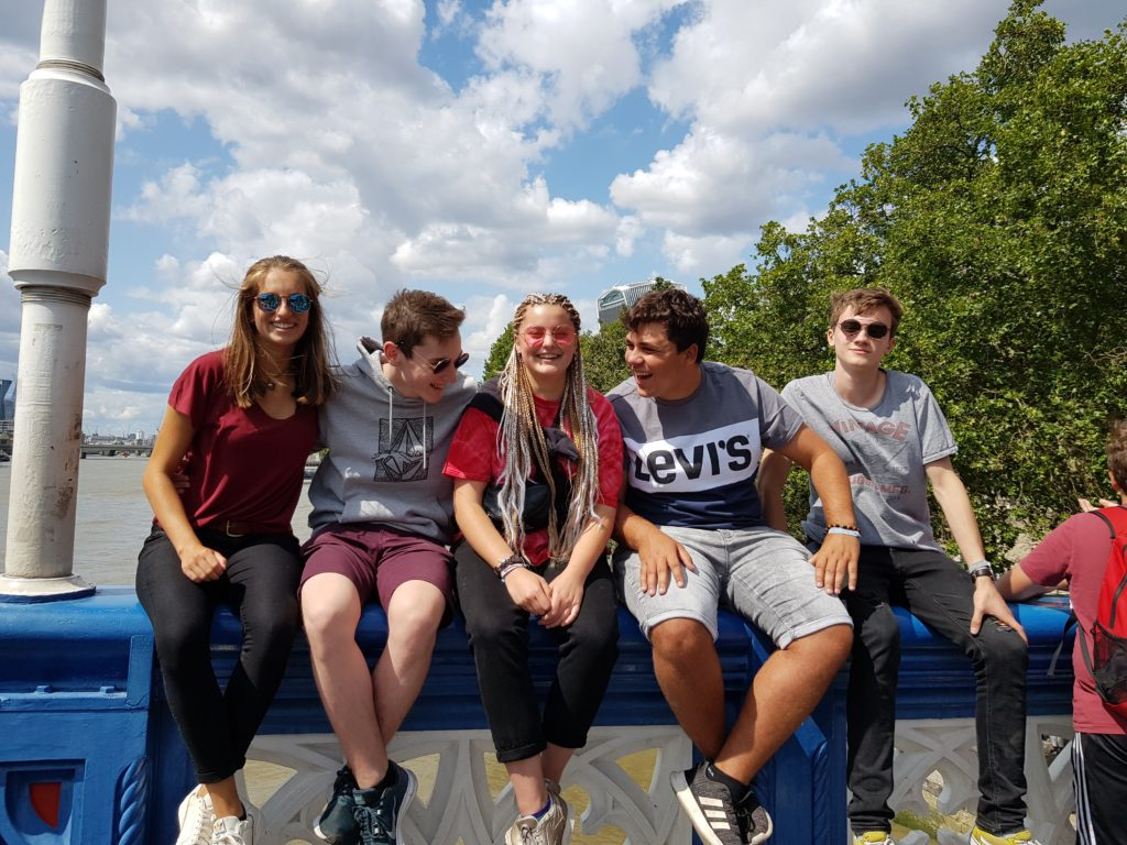 Fünf Jugendliche und Betreuer sitzen auf der Brüstung einer Brücke. Im Hintergrund sieht man einen Fluss. Die Jugendlichen und Betreuer*innen lachen miteinander und haben gute Laune.