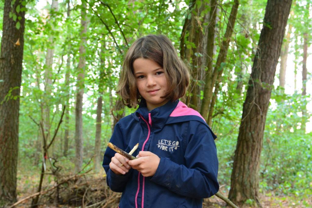 Ein Mädchen steht im Wald und hält zwei Zweige in der Hand, so als ob sie den einen mit dem anderen schnitzen möchte.