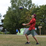Ein Jugendlicher und eine Jugendliche spielen auf einer Wiese Volleyball. Der Junge macht sich gerade bereit für die Annahme des Balles.