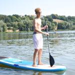 Ein Junge in Badehose steht auf einem Stand Up Paddle Board auf einem See. In der Hand hält er ein Paddel.