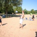 Mehrere Jugendliche spielen am Sandstrand Beachvolleyball.