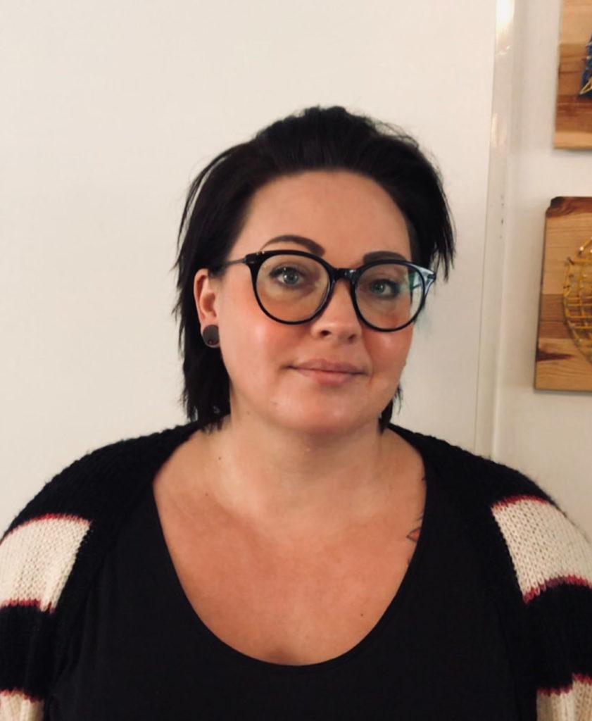 Portrait einer Frau mit kurzen schwarzen Haare und schwarzer Brille