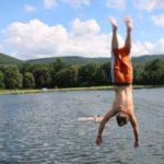 Ein Jugendlicher springt mit einem Salto in einen See. Das Foto zeigt den Moment in dem er gerade auf dem Kopf in der Luft ist.