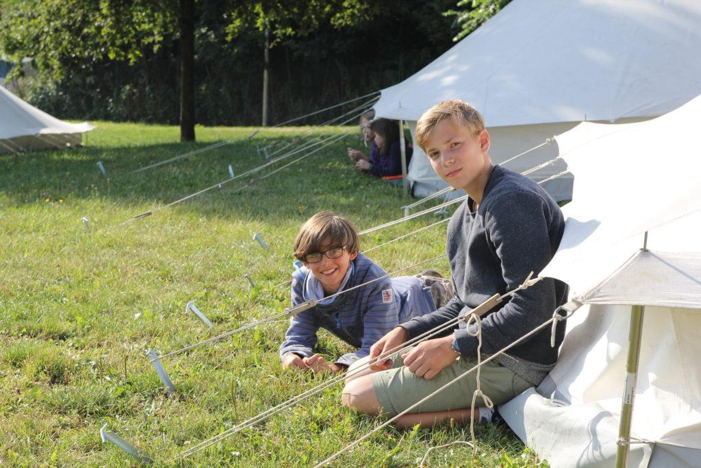 Zwei Jungen sitzen bzw. liegen auf dem Gras vor Weißzelten und schauen fröhlich.