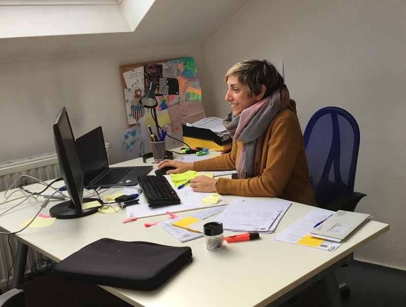 Foto einer Frau mit kurzen braunen Haaren. Sie sitzt an einem großen Schreibtisch und arbeitet an einem Computer.
